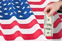 Stock Illustration of Composite image of hand holding hundred dollar bill
