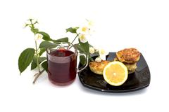 Tea, lemon and cheesecakes on a plate the drinks decorated with a flower bran Stock Photos