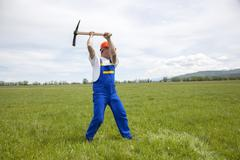 Worker With Pickaxe on a Green Meadow Kuvituskuvat
