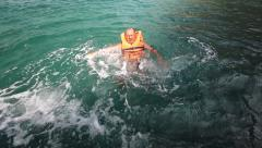 Scared sinking man in the sea with life jacket Stock Footage
