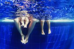 Underwater photo of happy family swimming in the blue pool Stock Photos