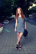 Curly haired women full body with handbag in her arms - stock photo