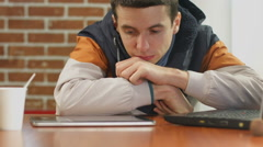 Bored student reading bad news on tablet, alone in cafe Stock Footage