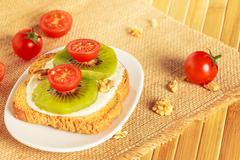 Toast with kiwi, cheese and cherry tomato Stock Photos