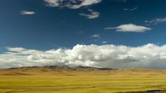 Huge meadow against backdrop of mountains, river and blue sky with clouds - stock footage