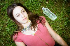 Relaxed young person (teenage girl) lying in grass and flowers with stretched Kuvituskuvat