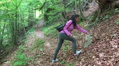 4k Girl builds pile of stones hiking cult Austria alps forest Stock Footage