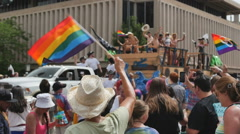 Supporter waves a rainbow flag at cowboys in gay pride parade Denver, colorado Stock Footage