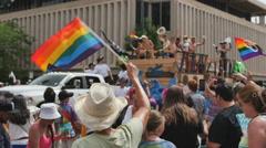 supporter waves a rainbow flag at cowboys in gay pride parade Denver, colorado - stock footage
