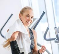 Attractive female with towel after Treadmill exercise Stock Photos