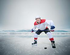 Expressive hockey player on the ice of a frozen lake Stock Photos
