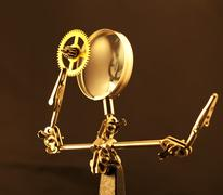 Stock Photo of magnifying glass & gold gear