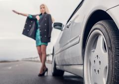 Lady in high heel shoes with broken car on the road Stock Photos