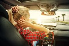 Beutiful blond girl comb her hair with a rearview mirror in car - stock photo