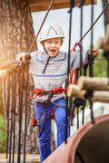 Happy boy on rope track in adrenalin park Stock Photos