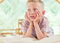 A little blonde boy lying on the cushion in the summerhouse Stock Photos