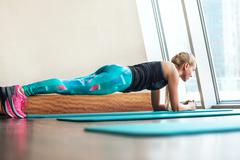 Stock Photo of Blonde female doing plank static exercise in gym