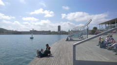 Relaxing on the seafront near Rambla de Mar in Barcelona Stock Footage