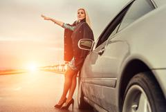 Lady in high heel shoes with broked car on the highway - stock photo
