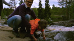 Mother holds child who rinses hands in mountain river Stock Footage