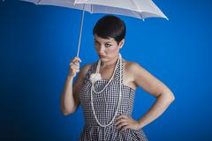 Stock Photo of Joyless, pinup girl style of the 50s with a white umbrella