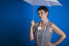 Stock Photo of Sad, pinup girl style of the 50s with a white umbrella