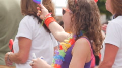 Excited happy little girl waves rainbow flag at Gay Pride parade slow motion Stock Footage