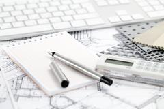Ruler calculator, metric folding ruler, notepad, pen and architectural drawin - stock photo