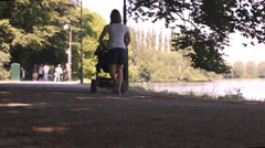 Mother with baby walking in park - stock footage