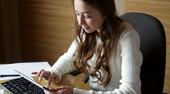 beautiful woman in a white sweater working at a computer - stock footage