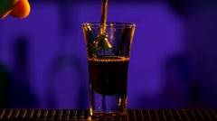 Barman continue pouring clear alcohol liquid, milk liquor, into a glass, shots Stock Footage