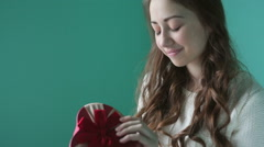 Beautiful young smiling woman with a gift in the form of heart in her hands - stock footage
