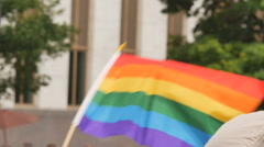 Rainbow flag waving with building and trees in background gay rights slow motion Stock Footage