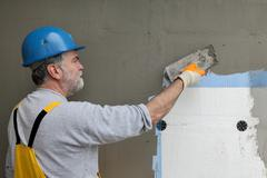 Wall insulation, spreading mortar over mesh and styrofoam Stock Photos