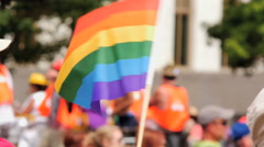 Waving Rainbow flag with float of gay pride supporters in background slow motion Stock Footage