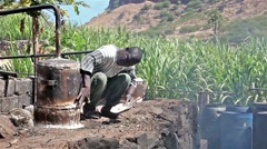 Man making sugar cane moonshine in Cape verde Africa Stock Footage