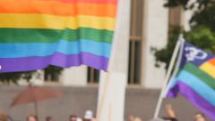 rainbow flag waving with protest signs and flags in the background slow motion - stock footage