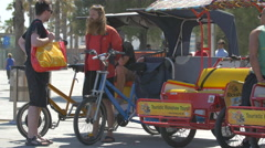 Two men talking near the rickshaw tour rentals in Barcelona - stock footage