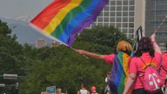 Gay Pride Parade marchers supporters wave rainbow flags Rocky Mountains slo mo Stock Footage