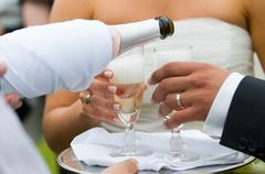 bottle of champagne pooring in to glasses - stock photo