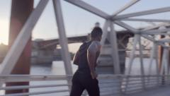 Male Athlete Runs Down Pedestrian Bridge, Along Waterfront In Portland (4K) Stock Footage