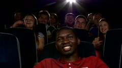 Happy multiethnic young men watching movie in the theatre - stock footage