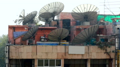 An array of large satellite dishes sit atop a skyscraper in central New Delhi Stock Footage