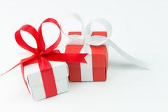 Two gift boxes with ribbon over white background - stock photo