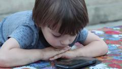 The kid plays download application on a smartphone close-up Stock Footage