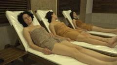 Three female enjoy on deck chairs in lyxury spa complex. UHD 4K steadycam sto Stock Footage