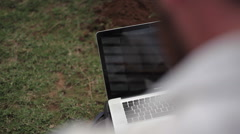 Using a computer in the field outdoors, close up, shallow DOF Stock Footage
