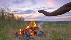 The hands near bonfire by picturesque sky background - stock footage