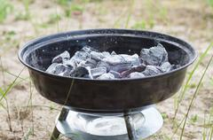 Smouldering charcoal in small grill - stock photo