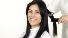 Female model getting long hair straightened medium shot Stock Footage